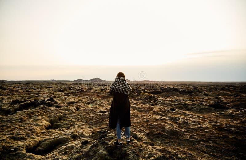 Una chica joven se coloca con ella detrás y toma las imágenes del paisaje fotografía de archivo libre de regalías
