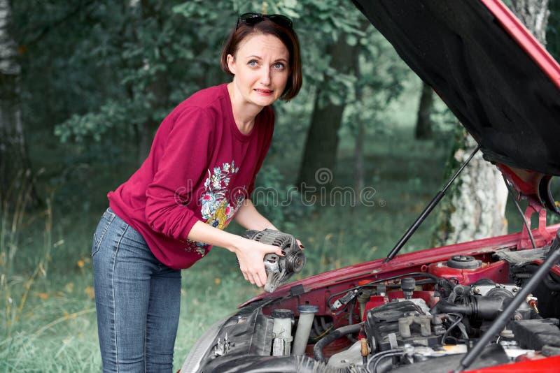 Una chica joven se coloca en un coche quebrado y lleva a cabo un mún recambio, un generador eléctrico, no entiende cómo reparar fotos de archivo libres de regalías