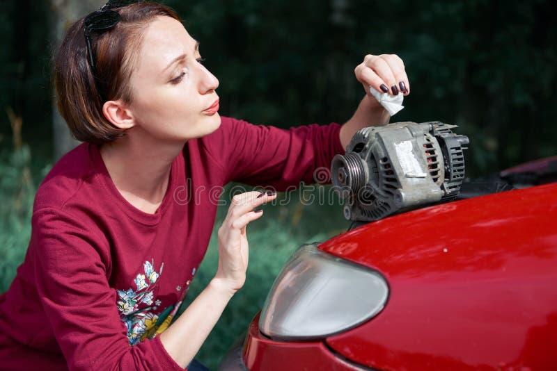 Una chica joven se coloca en un coche quebrado y lleva a cabo un mún recambio, un generador eléctrico, no entiende cómo reparar,  foto de archivo