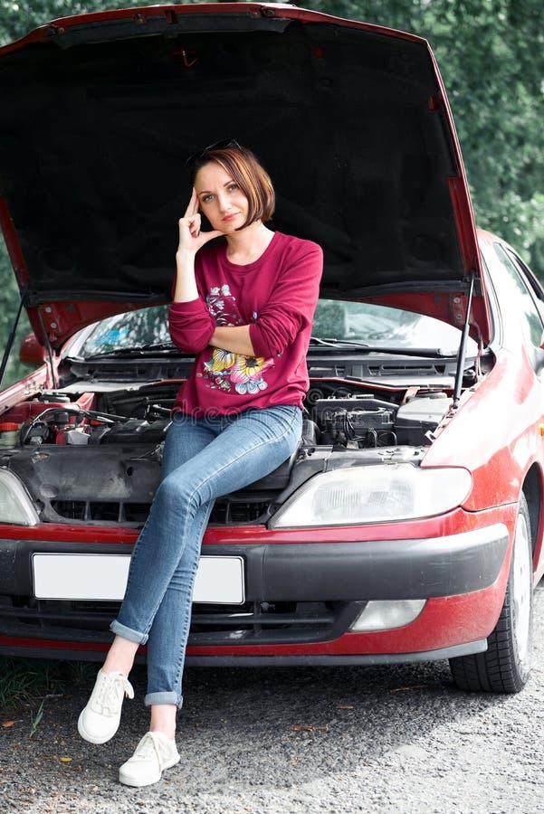 Una chica joven se coloca en un coche quebrado y mira el motor, no entiende cómo reparar imágenes de archivo libres de regalías