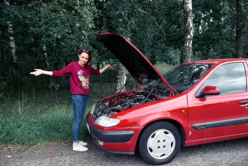Una chica joven se coloca en un coche quebrado y mira el motor, no entiende cómo reparar foto de archivo