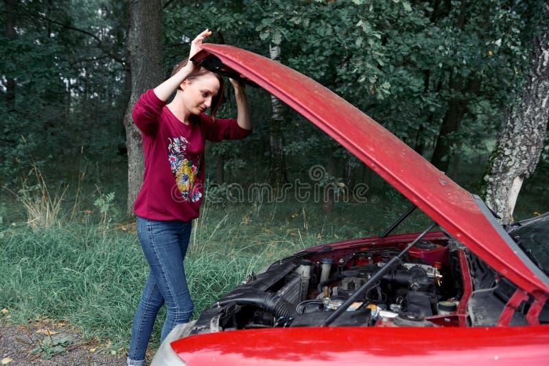 Una chica joven se coloca en un coche quebrado y mira el motor, no entiende cómo reparar imagen de archivo