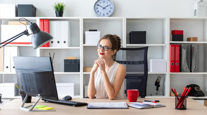 Una chica joven se está sentando en el escritorio en la oficina fotografía de archivo