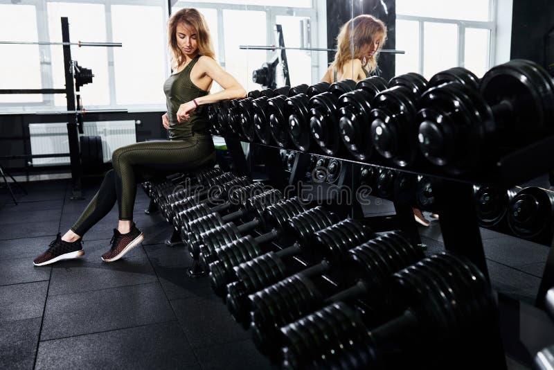 Una chica joven se está sentando en una pesa de gimnasia imagen de archivo