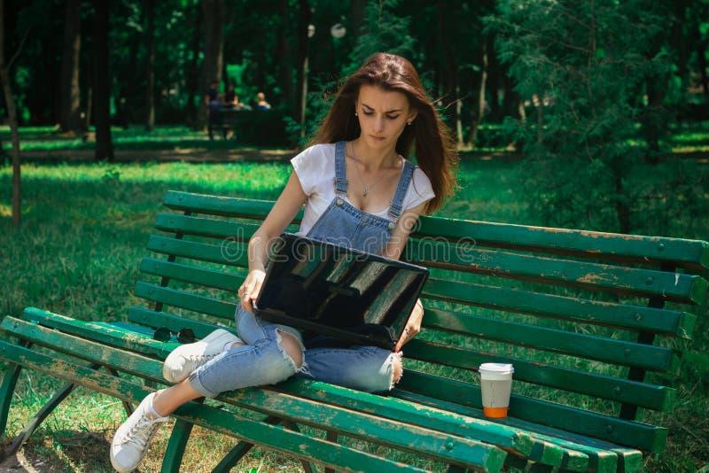Una chica joven se está sentando en un parque e imprime en un ordenador portátil fotografía de archivo