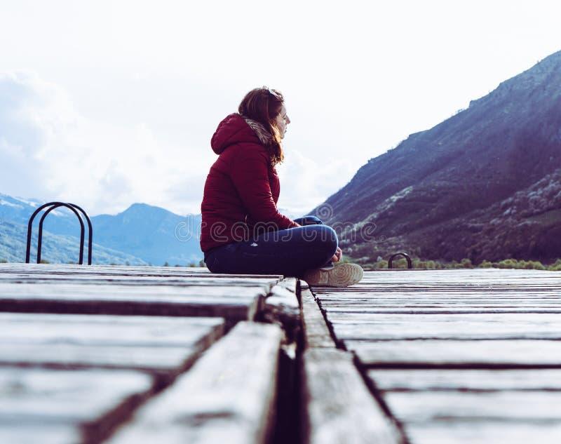 Una chica joven se sienta al borde de un embarcadero de madera y de miradas en la distancia rodeada por las monta?as en el lago P imagen de archivo