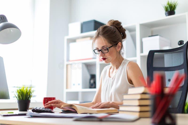 Una chica joven se sienta en una tabla del ordenador y sostiene un libro abierto en sus manos e impresiones en el teclado foto de archivo libre de regalías