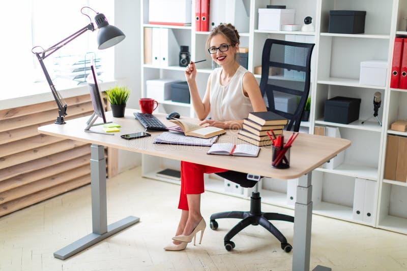 Una chica joven se sienta en un escritorio del ordenador y sostiene un libro abierto y un lápiz en sus manos fotos de archivo