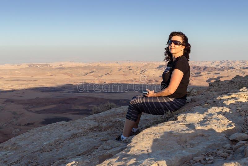 Una chica joven sola se sienta en el acantilado de la montaña en la puesta del sol en el desierto de Judean en Israel imagen de archivo libre de regalías