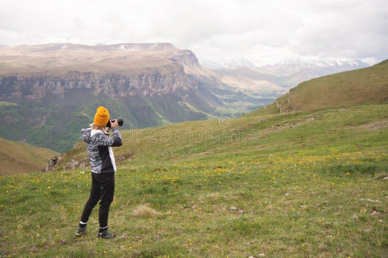 Una chica joven toma imágenes de una meseta encima de una alta montaña en un día nublado Opinión la muchacha detrás fotografía de archivo