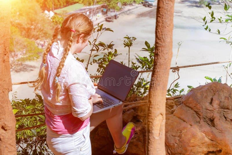 Una chica joven trabaja con un ordenador port?til en la monta?a que pasa por alto la selva tropical y la playa Trabajo y viaje fr fotos de archivo libres de regalías