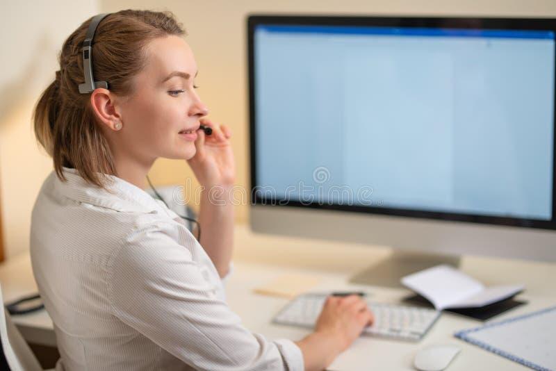 Una chica joven trabaja en un centro de atención telefónica Para un lugar de trabajo con un teléfono Un micrófono con un micrófon fotos de archivo libres de regalías