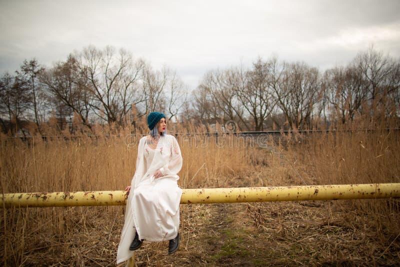 Una chica joven vestida en un vestido largo blanco, sent?ndose en un tubo, cerca de un campo de trigo foto de archivo