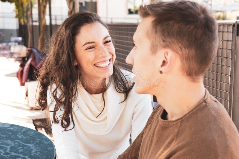 Una chica y un niño están coqueteando, habla con ella y ella se ríe feliz, se centra en la expresión de la chica - Cortejo y amor imagen de archivo libre de regalías