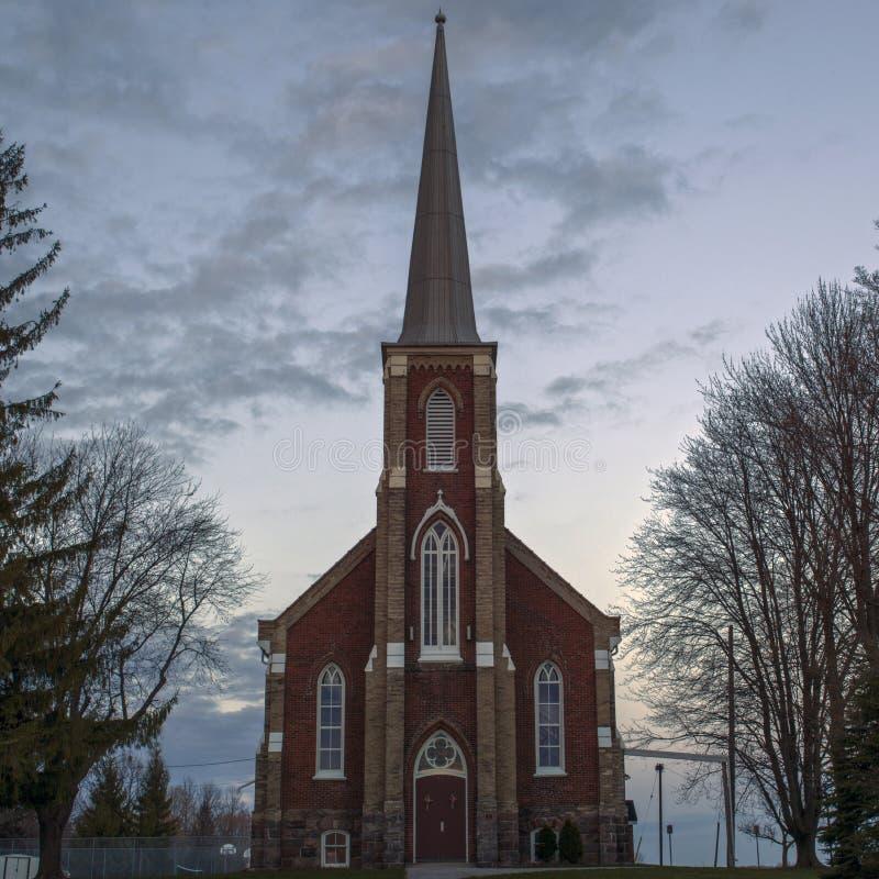 Una chiesa del campanile del mattone rosso al crepuscolo fotografia stock libera da diritti