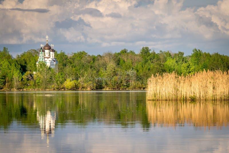 Una chiesa ortodossa bianca che riflette nell'acqua fotografia stock