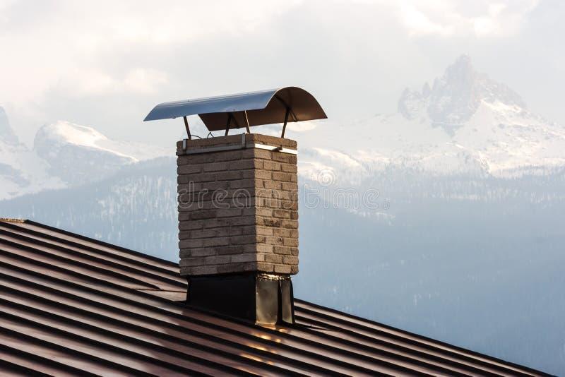 Una chimenea en el tejado de una casa en Cortina d'Ampezzo, dolomías, Italia imagen de archivo libre de regalías