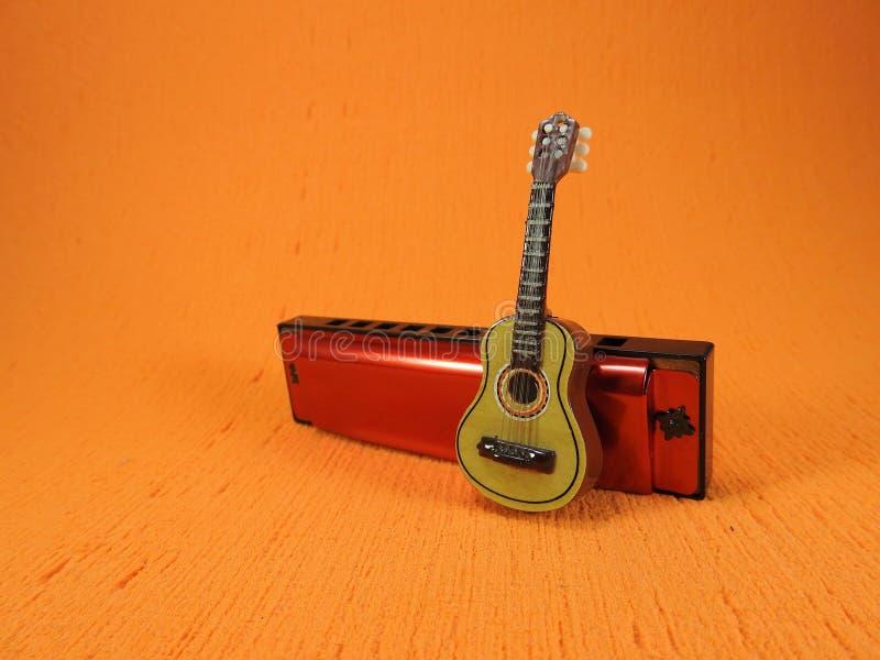 Una chitarra acustica miniatura propped su su un'armonica diatonica immagini stock