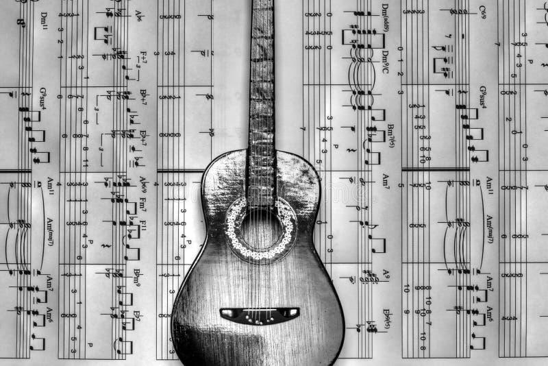 Una chitarra che riposa sulle note musicali fotografia stock