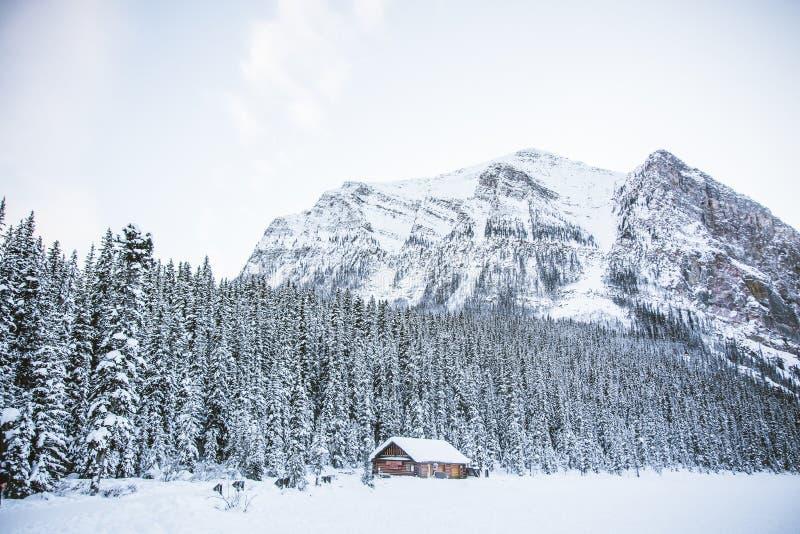 Una choza en un campo nevoso con montañas rocosas y un bosque fotografía de archivo libre de regalías