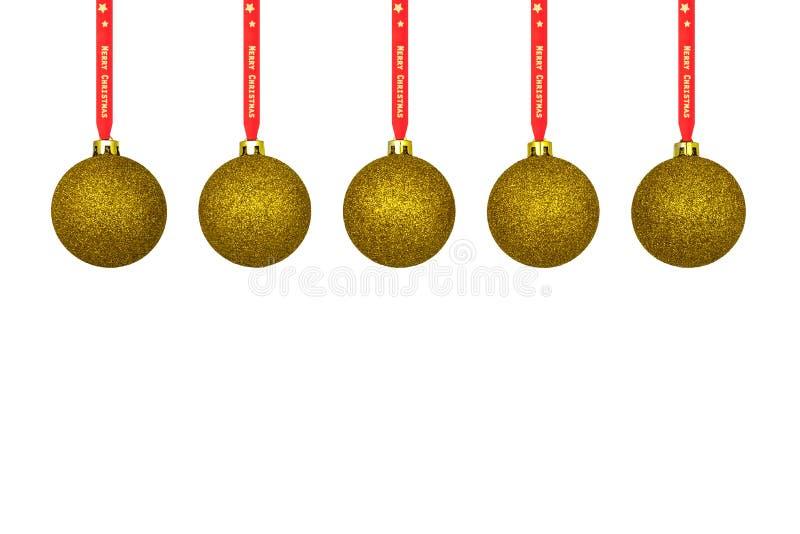 Una chuchería de la Navidad del oro que cuelga en una cinta roja, aislada en un fondo blanco con un espacio de la trayectoria que fotografía de archivo libre de regalías