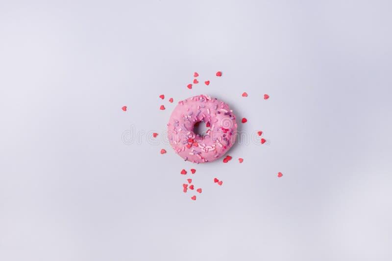 Una ciambella con glassa sulle guarnizioni di gomma piuma saporite dolci rosa pastelli del fondo blu copia la disposizione piana  fotografia stock