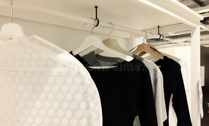 Una cierta variedad de ropa que cuelga en alameda de compras con variedad imagen de archivo