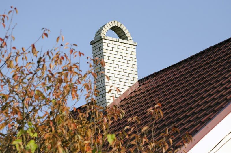 Una ciminiera di mattoni bianchi sul tetto marrone della casa immagini stock