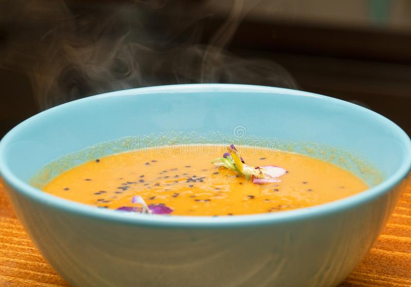 Una ciotola con la cottura a vapore della minestra calda della zucca in una ciotola blu-chiaro guarnita con i fiori freschi della fotografie stock