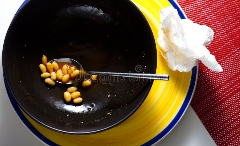 Una ciotola di fagioli in salsa quasi vuota fotografia stock