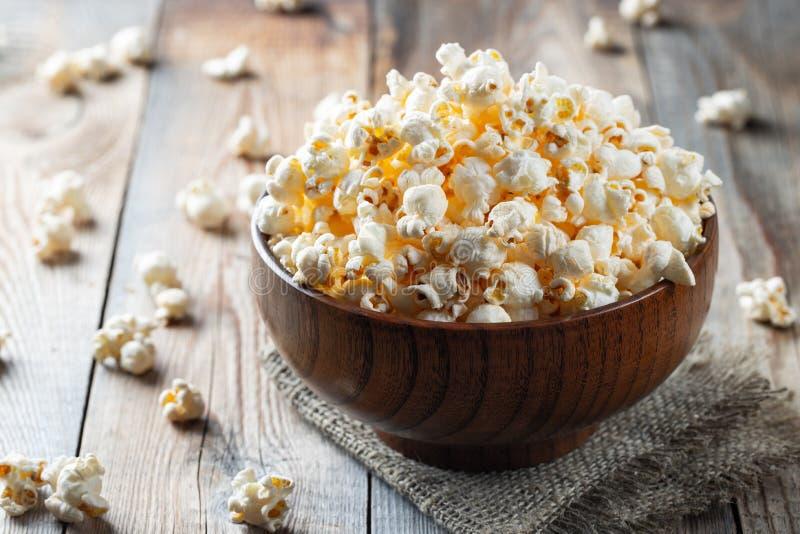 Una ciotola di legno di popcorn salato alla vecchia tavola di legno Fondo scuro Fuoco selettivo fotografie stock