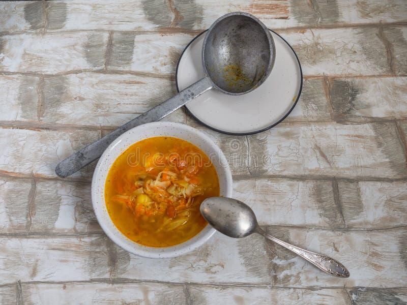 Una ciotola di minestra con una vecchia siviera della latta di Selenin fotografia stock