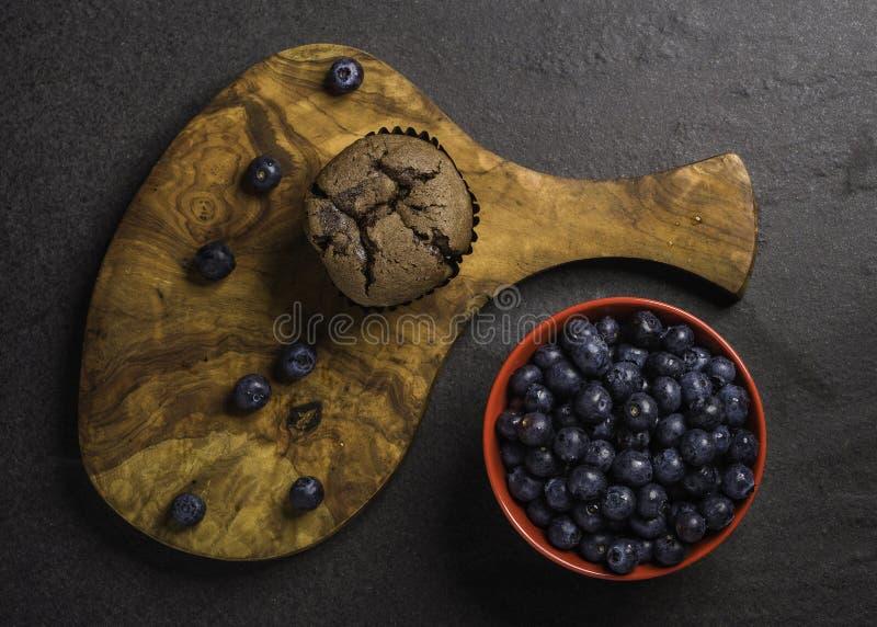Una ciotola rossa di mirtilli organici freschi su un fondo scuro della roccia con un muffin libero di legno del cioccolato del gl fotografia stock libera da diritti