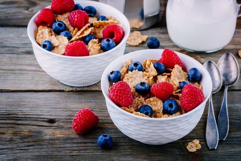 Una ciotola sana della prima colazione Intero cereale del grano con i mirtilli ed i lamponi freschi su fondo di legno fotografie stock libere da diritti