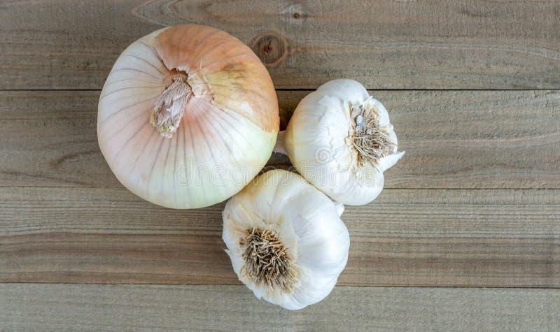 Una cipolla dolce e 2 lampadine dell'aglio su un fondo di legno immagine stock libera da diritti