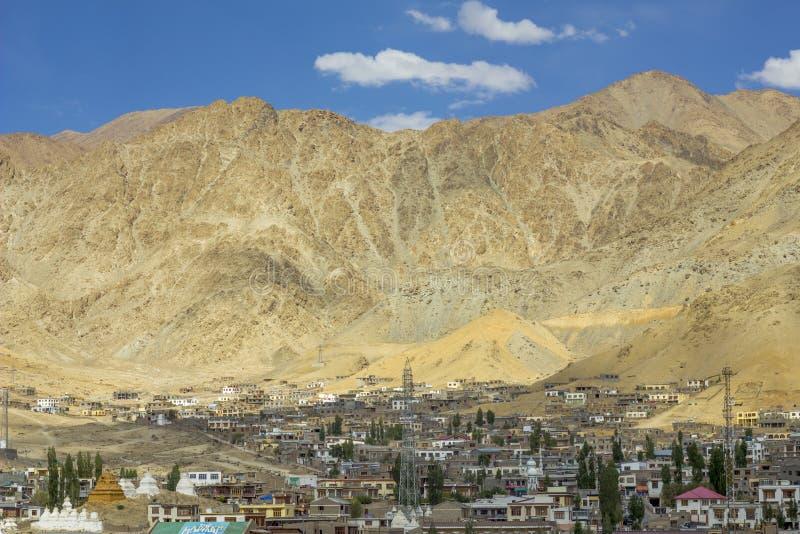 Una ciudad debajo de una montaña arenosa y de un cielo azul imagen de archivo