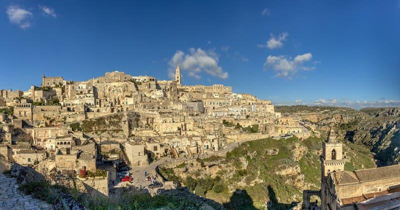 Una ciudad en un afloramiento rocoso y un complejo de las viviendas de cueva talladas foto de archivo libre de regalías