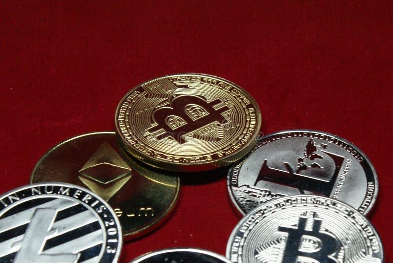 Una colecci?n de monedas del cryptocurrency en un fondo del rojo del terciopelo imagenes de archivo