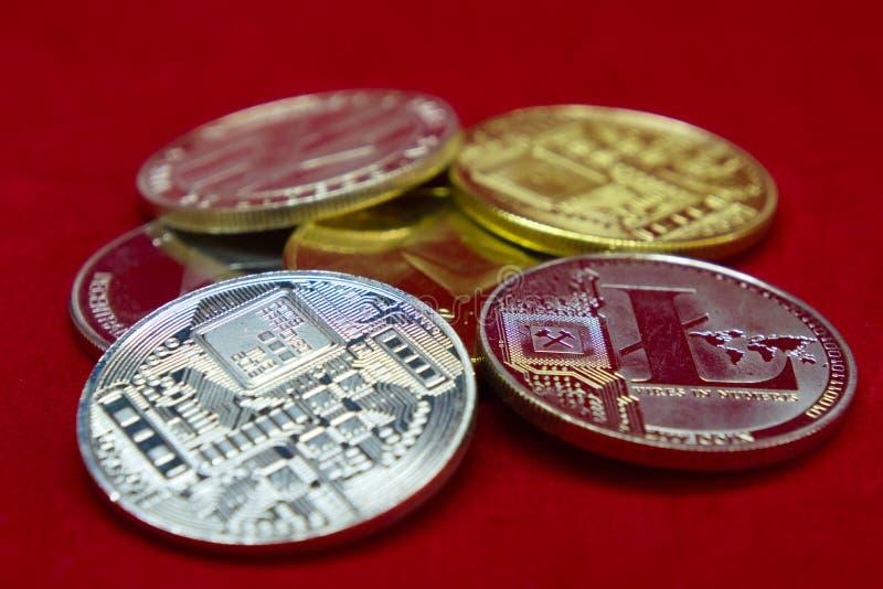 Una colección de monedas del cryptocurrency de la plata y del oro en un fondo rojo del terciopelo fotografía de archivo libre de regalías