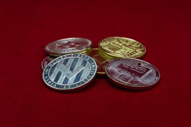Una colección de monedas del cryptocurrency de la plata y del oro en un fondo rojo del terciopelo imagenes de archivo