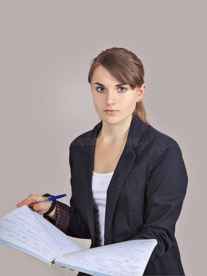 Una colegiala bastante adolescente está escribiendo con la pluma en los cuadernos aislados en fondo gris fotografía de archivo