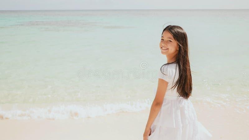 Una colegiala filipina encantadora en un vestido blanco está caminando a lo largo de una playa arenosa blanca Disfrutar del paisa imágenes de archivo libres de regalías