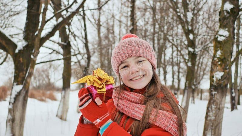 Una colegiala joven hermosa que se coloca en un bosque nevoso en el invierno toma un regalo alegre de las manos de un amigo fotos de archivo libres de regalías