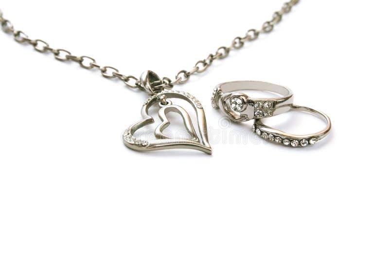 Una collana dei due cuori e due anelli fotografia stock libera da diritti