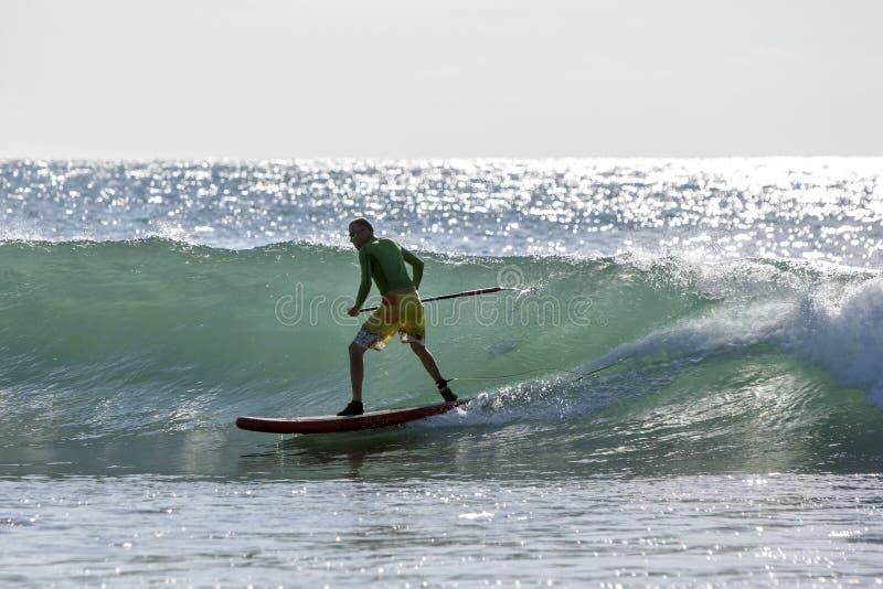 Una colocación encima de la persona que practica surf de la paleta monta una onda de la rotura del punto en la bahía de Arugam en fotos de archivo libres de regalías