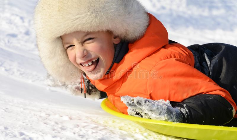 Una colocación sonriente del muchacho en su trineo, retrato del primer Diversión del invierno foto de archivo libre de regalías