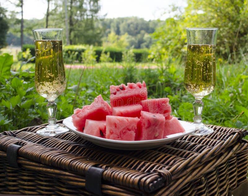 Una comida campestre con una bebida y una fruta en el parque en un día de verano soleado fotografía de archivo
