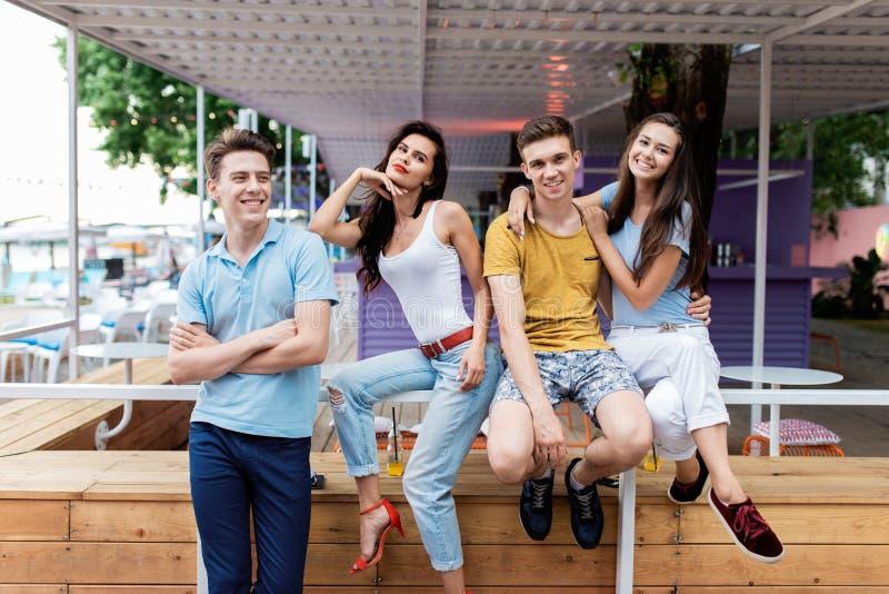 Una compañía de amigos apuestos es de risa y que se sienta en la verja en el café agradable del verano Entretenimiento, teniendo fotos de archivo libres de regalías