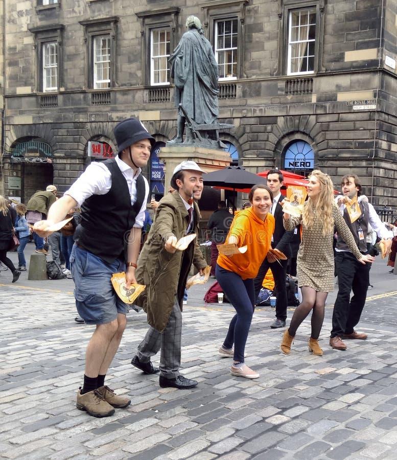 Una compañía de ejecución en el festival de la franja de Edimburgo que distribuye los aviadores en la milla real foto de archivo libre de regalías