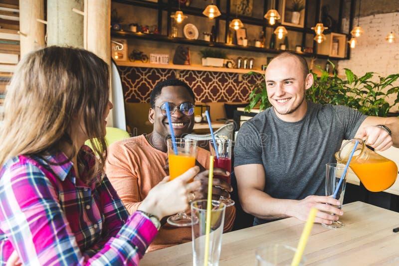 Una compa??a de la gente joven que se divierte, bebidas de consumici?n, c?cteles, jugos en un caf? mejores amigos de la reuni?n fotos de archivo